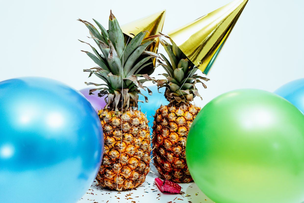 photo of pineapples and party hats, balloons for the new year