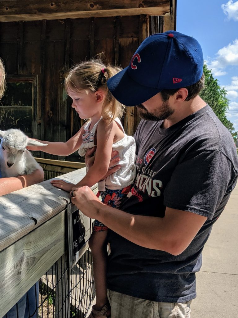 photo of k petting the goat | our trip to storybook land in aberdeen sd