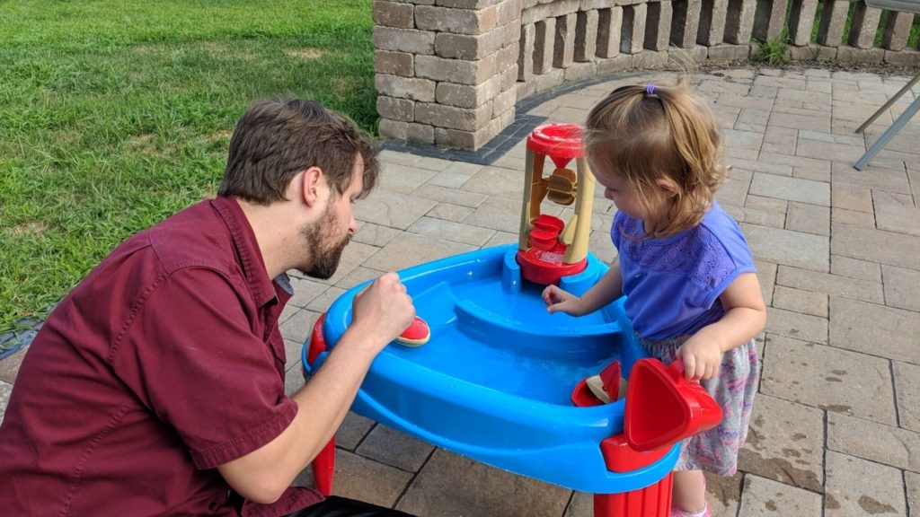 dad playing at the water table with toddler, one of our kids' favorite outdoor activities with family or alone