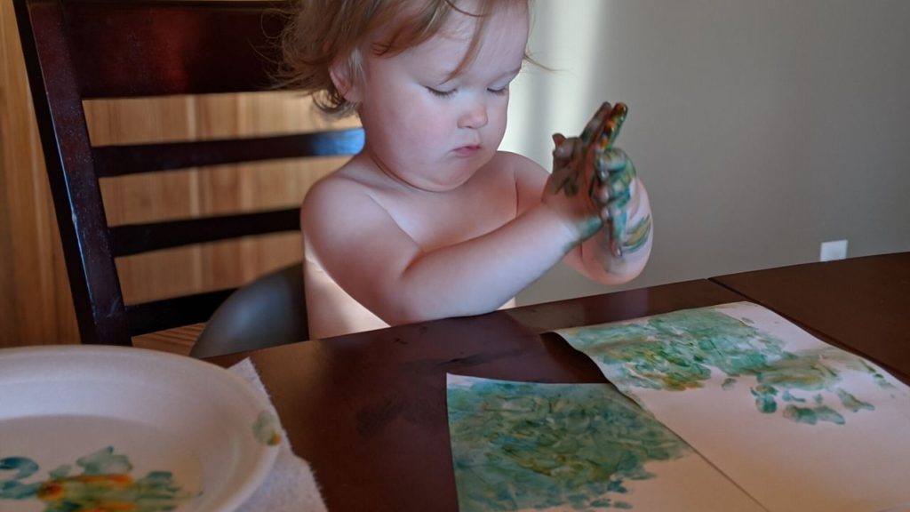 photo of toddler playing with finger paints